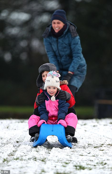 Daniel Brym, aged 8, and his sister Emma, aged 4, and their mother Alicja, sledging on Camp Hill, Woolton, Liverpool, after snow fell overnight.