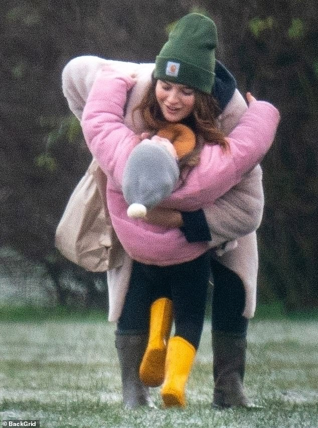Close:At one point she affectionately lifted her young daughter, who wore a pink quilted jacket and a grey bobble hat while out with the reality TV personality