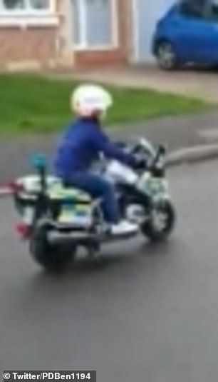 A four-year-old boy rides his brand new toy police motorbike up the road