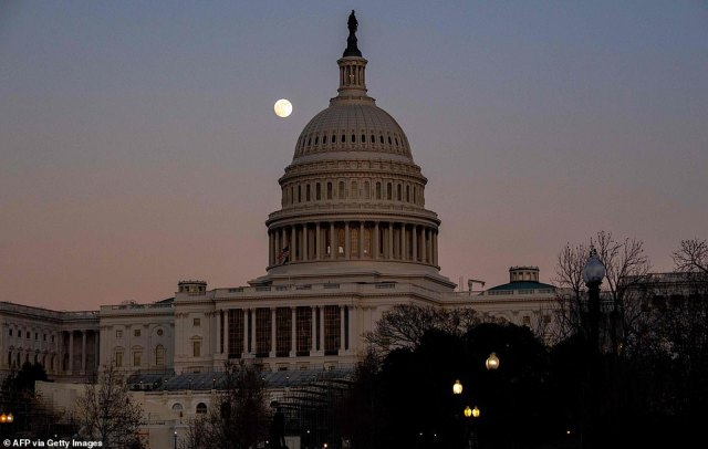 The moon rises over the US Capitol Dome at sunset in Washington, D.C.