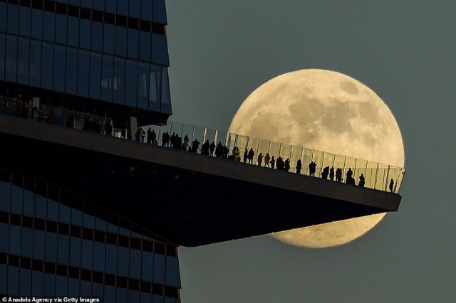 The gull moon rises behind people standing on the Edge, the outdoor observation deck in Manhattan, New York City