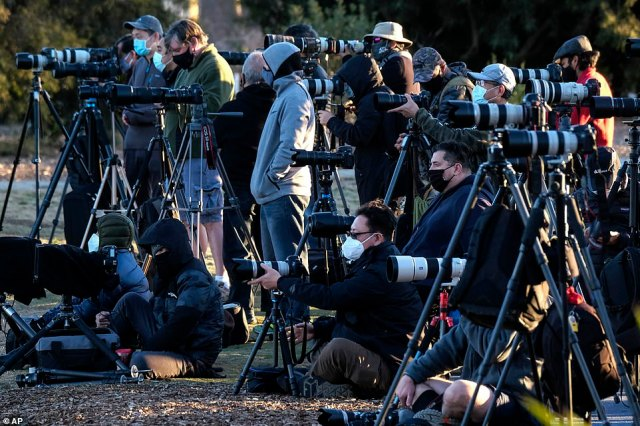 Photographers set their equipment as they are waiting to capture the moon rising over snow covered mountains, behind the downtown Los Angeles skyline at Kenneth Hahn State Recreation Area in Los Angeles on Tuesday