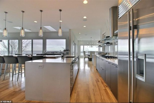 Dining: A stunning fashionable kitchen features modern lighting, floor-to-ceiling windows and sleek appliances, coupled with a 10-seater dining room table.