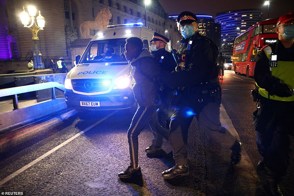Police officers detain a man at the anti-lockdown protest on the South Bank, London, during the night