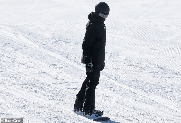 Hitting the slopes: He was hitting the slopes on the snowboard in all black.