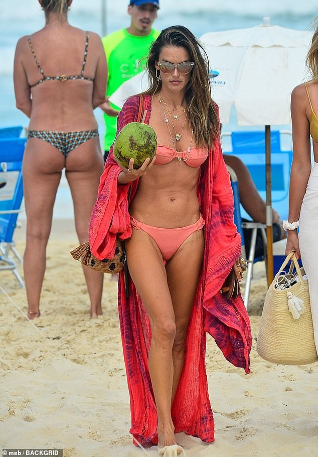 Glowing:The supermodel, 39, put her toned physique on display in a tiny pink two piece that highlighted her glowing tan