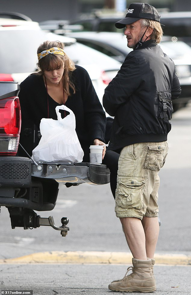 Sean Penn keeps it casual in black bomber as he has parking lot picnic with wife Leila George in LA