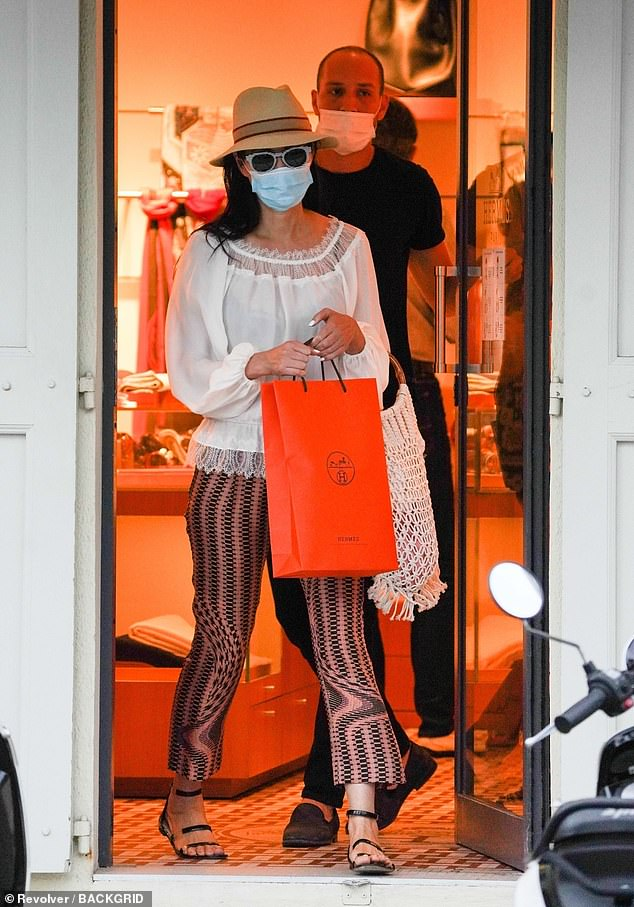 Hey, big spender: Wendi Deng and her hunky mystery companion were spotted shopping on the French-Caribbean island ofSaint Barthélemy on Saturday