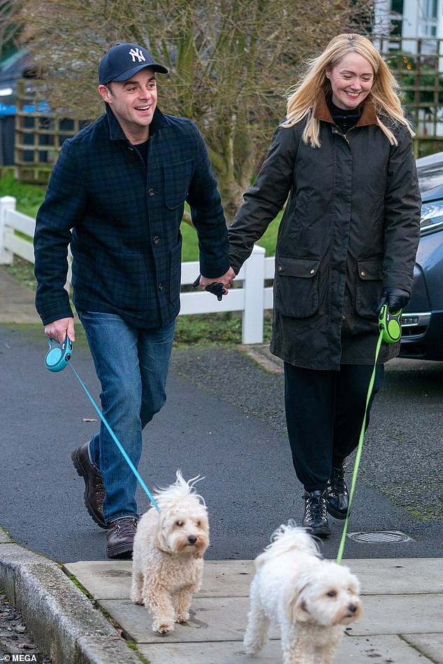 Loved-up: The TV presenter, 45, and the personal assistant, 43, couldn't stop smiling as they held hands while taking their dogs for a walk on Sunday