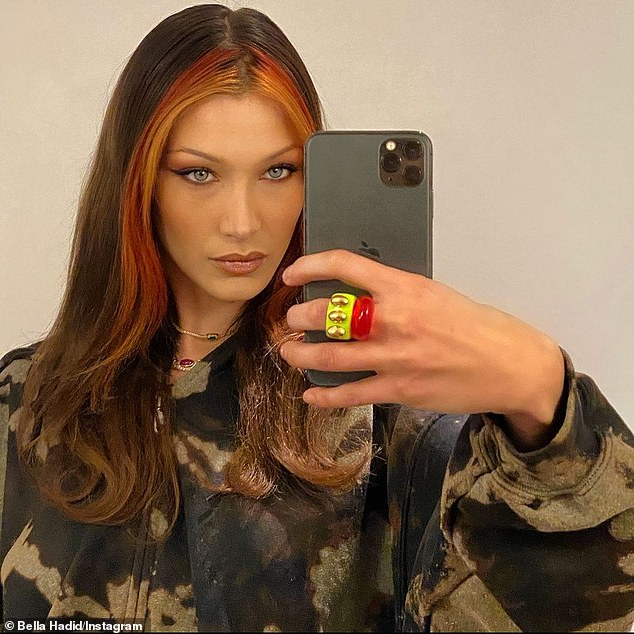 Casual glam: Bella Hadiddressed down her glam look Sunday with a casual acid wash hoodie in an impromptu mirror selfie she posted to Instagram, after revealing a new red hairdo