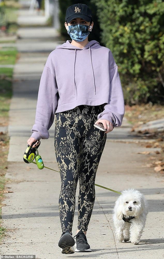 Puppy love: Lucy Hale slipped into some skintight black snakeskin leggings and a cropped lilac hoodie Sunday, as she was spotted getting in a walk with her dog Elvis at home in Los Angeles