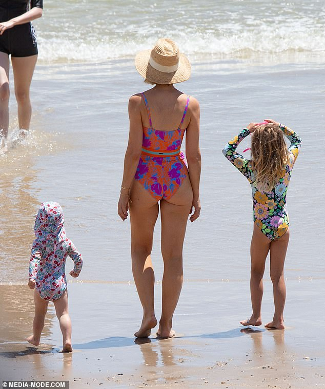 Gorgeous: Carrie's patterned swimsuit featured a waist-cinching belt and spaghetti straps
