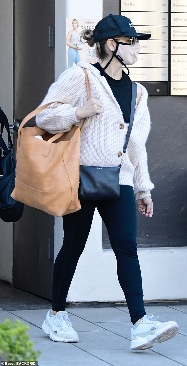 Casual: Sarah Michelle Gellar started her day Sunday at the gym, heading out in a black t-shirt and black leggings along with a white knit cardigan
