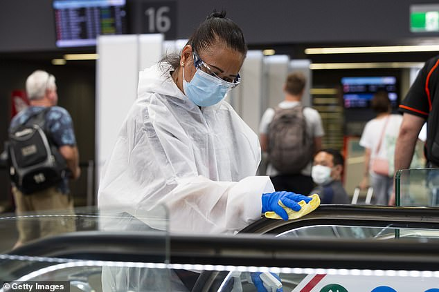 Airport staff disinfect the Perth Airport terminal escalators on December 8. Western Australia will shut its border to all jurisdictions if the Covid outbreak spreads out of NSW and Victoria