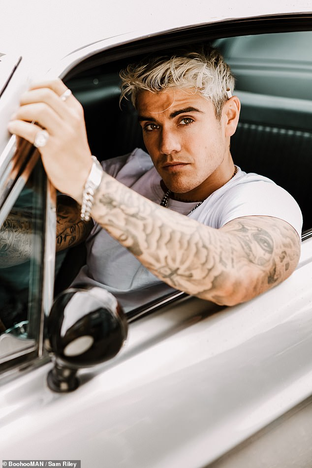 Pose:In another image, Luke, whose signed calendar costs £15.99, posed behind the wheel of a luxury car