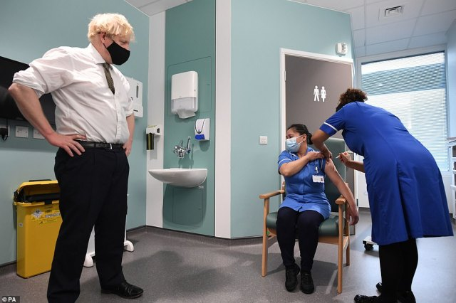 Prime Minister Boris Johnson watches as Jennifer Dumasi is injected with the Oxford/AstraZeneca Covid-19 vaccine during a visit to Chase Farm Hospital in north London this morning