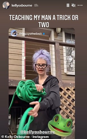 Doing her best: In an amusing video, Kelly tried to show Erik how she puts away her hose, while she wrote over the video: 'Teaching my man a trick or two'