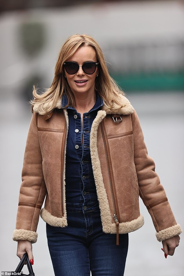 Stylish: Amanda Holden wore a denim jumpsuit and heels with a shearling aviator jacket as she returned to work at Heart FM in London on Monday