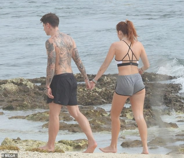 Beach buddy: The couple of over a year were seen strolling hand and hand by the shoreline before getting in a quick workout