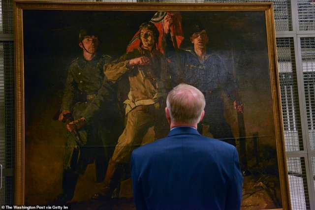 """Dr. Charles H. Cureton, director of Army museums, discusses Hans Schmitz-Wiedenbruck's"""" German Military Services,"""" a 1941 oil painting on canvas that is being housed at Fort Belvoir"""