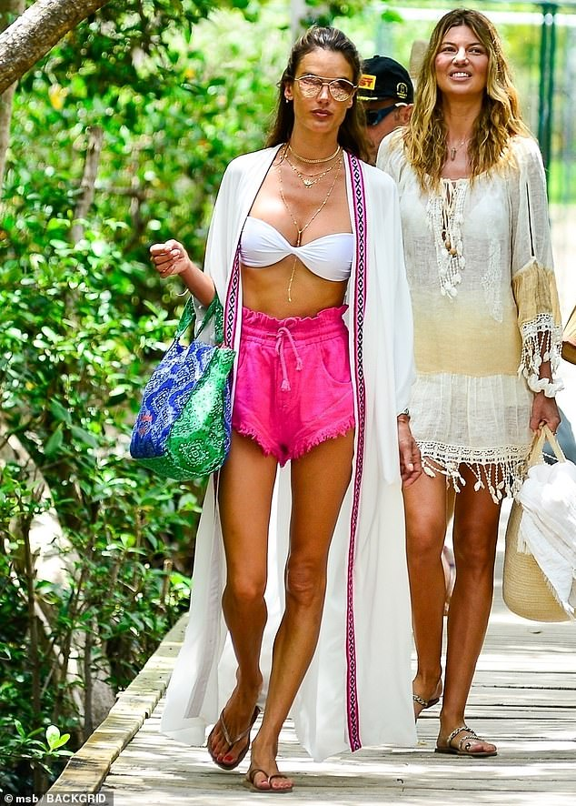 Hanging out: The supermodel posed for the cameras as she made her way down a wooden pathway that cut through dense tropical scenery with a pretty friend