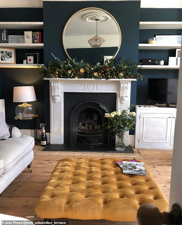 The couple styled their renovated living room with a Laura Ashley sofa, a mustard ottoman and a West Elm coffee table as well as two antique French button back armchairs