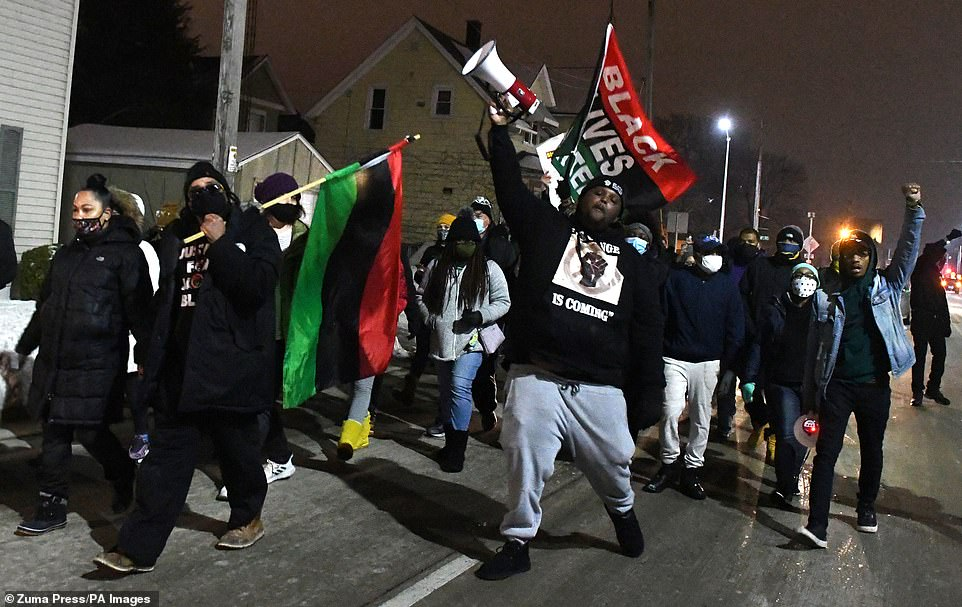 Jacob Blake's uncle, carries the Pan-African or Marcus Garvey flag as he leads several dozen protestors, in a march