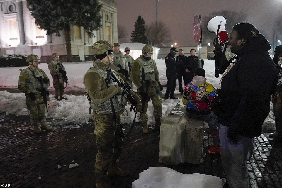 A group of protesters with a megaphone protest near a group of National Guard members outside a museum late Tuesday
