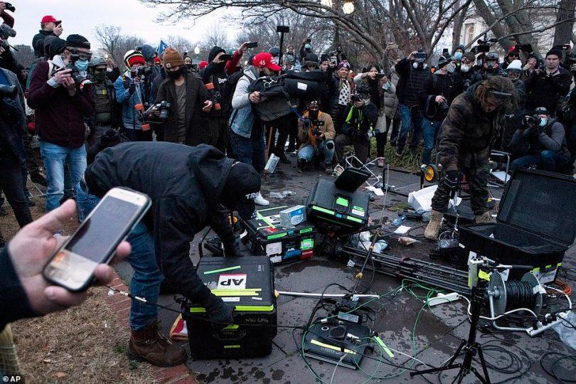 Demonstrators break TV equipment outside the the U.S. Capitol on Wednesday, Jan. 6, 2021, in Washington