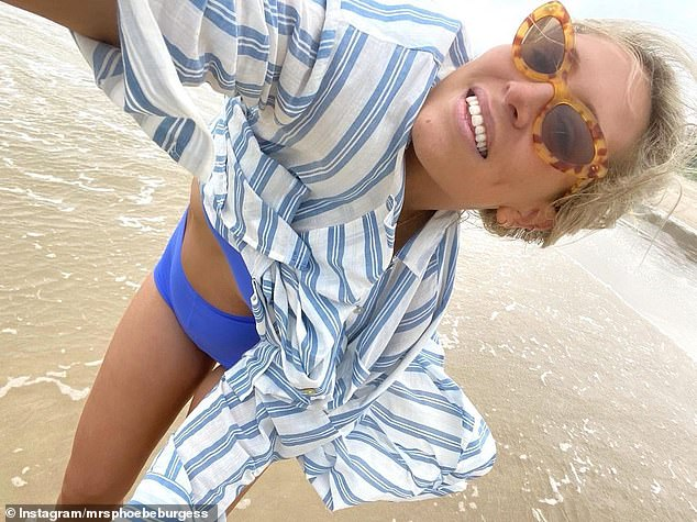 Former football WAG Phoebe Burgess gets blown away on the beach at Port Macquarie