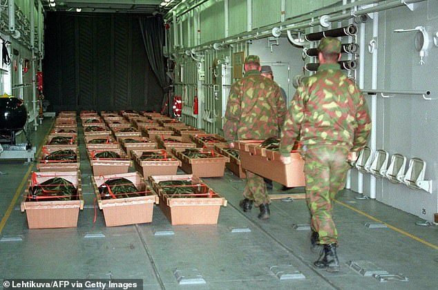 Pictured: Finnish Army recruits carry some of the victims of the Estonia ferry disaster into an amphibious landing craft for transfer from the island of Uto to the mainland in September 1994