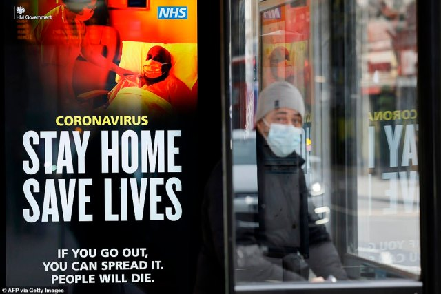 "A commuter wears a facemask as he sits in a bus shelter with signage promoting ""Stay Home, Save Lives"" in central London"