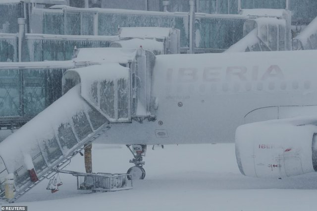 The heavy snowfall caused by Storm Filomena completely covers this parked plane at Madrid's Barajas Airport, which has suspended all flights
