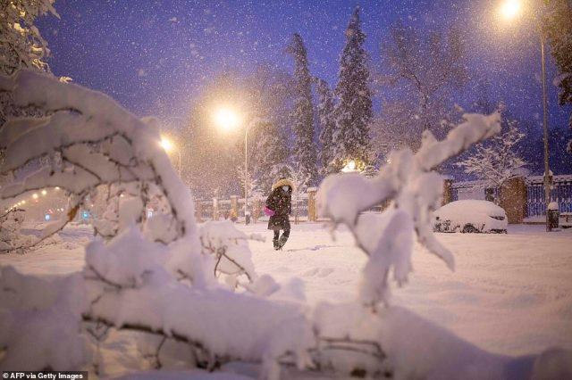A woman wrapped up in warm clothing braves the heavy snowfall as she walks through a street in Madrid this morning