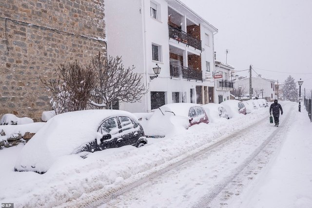 The snow has been falling so hard around Madrid that it now sits in mounds almost half the height of a car