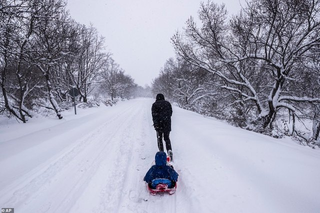 With people in Madrid taking to the streets to enjoy the unusually heavy snowfall, this parent was spotted dragging their child along a snow-covered road on a sled