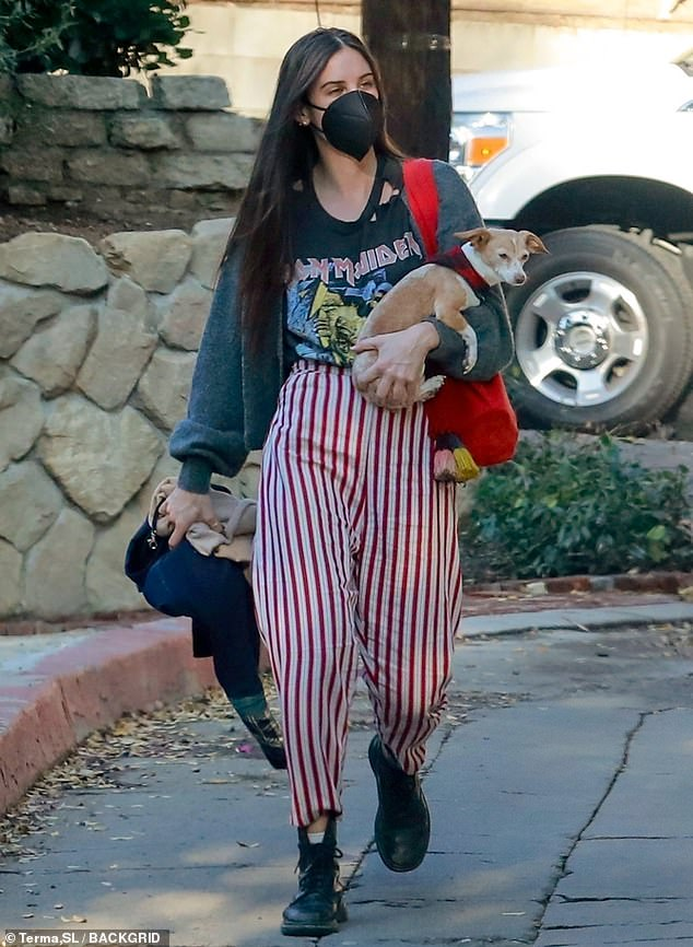Stylish: Willis was spotted wearing a distressed black t-shirt featuring a graphic for the heavy metal legends Iron Maiden and red pinstripe pants