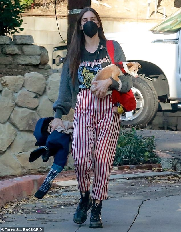 Scout Willis wears a heavy metal shirt and striped pants while visiting a friend with her dog