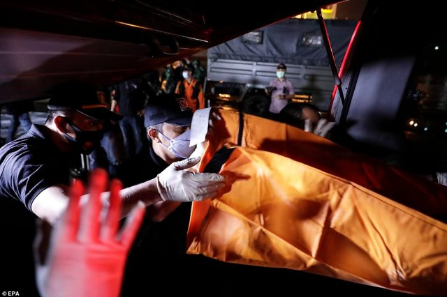 Pictured:Indonesian Disaster Victim Identification (DVI) officers unload a bodybag with the suspected remains of a Sriwijaya Air passenger found on the water off Jakarta, at Tanjung Priok port in Jakarta, Indonesia, 10 January