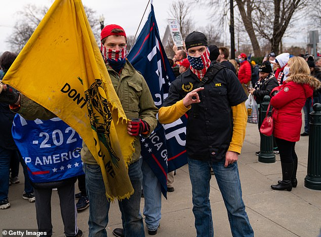Members of the Proud Boys making the okay sign and holding Trump 2020 and the Gadsden flag just before the riot at the U.S. Capitol on Wednesday