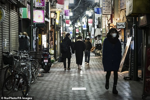 Japan's Ministry of Health, Labor and Welfare has reported the new strain to the World Health Organization.  Pictured: People wear masks on the street in Tokyo