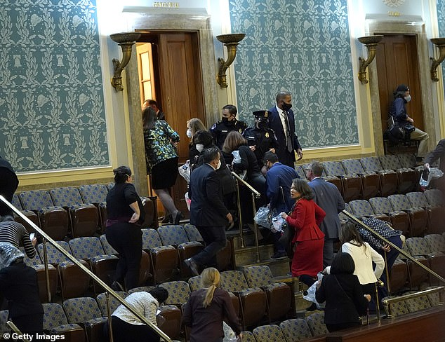 Members of Congress rush to evacuate the chamber as protesters attempted to enter on Wednesday