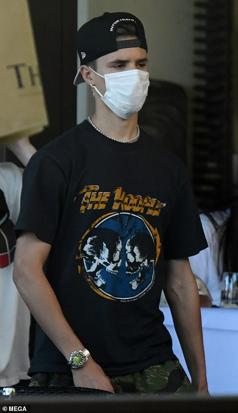Following in their father's cool footsteps: Romeo, 18 (pictured), and Cruz coordinated in white face masks, graphic T-shirts and baseball caps worn backwards