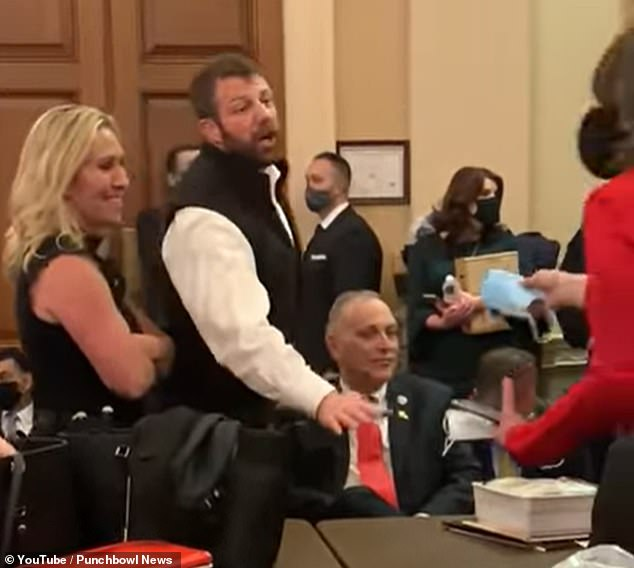 The video showed several Republican lawmakers wearing no masks - including Reps Andy Biggs (seated right), Marjorie Taylor Greene (left) and Markwayne Mullin (center)