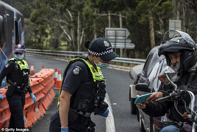 A new 'traffic light' system is being introduced to clear up Victorians' confusion about where they can travel in Australia. Pictured is a motorist passing through a border checkpoint in Mallacoota in the state's East Gippsland region