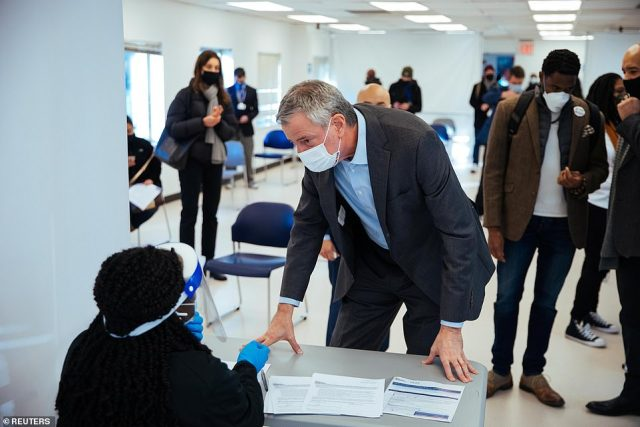 De Blasio pictured talking to staff during his visit to the Bathgate Post Office vaccination facility in the Bronx