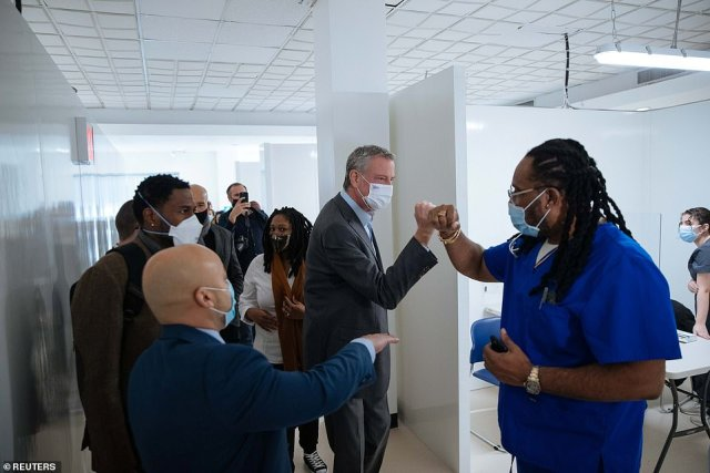 New York City Mayor Bill de Blasio greets nurse practitioner Alexander Gumbs during a visit to the Bathgate Post Office vaccination facility in the Bronx on Sunday