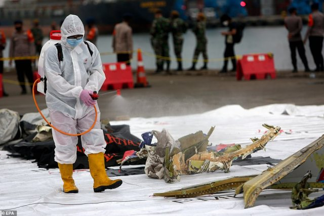 A medical officer sprays disinfectant onto the washed up debris as rescuers desperately search for survivors