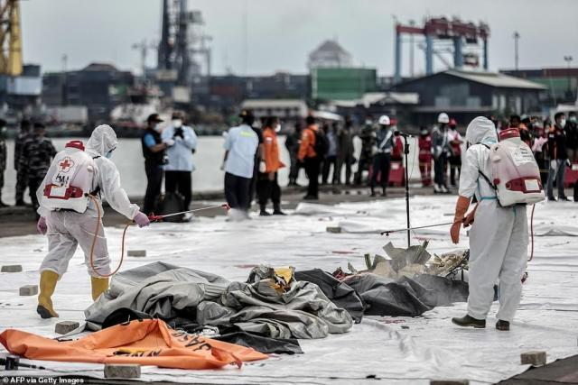 Health workers spray disinfectant over body bags containing human remains recovered from the crash site of Sriwijaya Air flight SJ182 at the port in Jakarta on January 10
