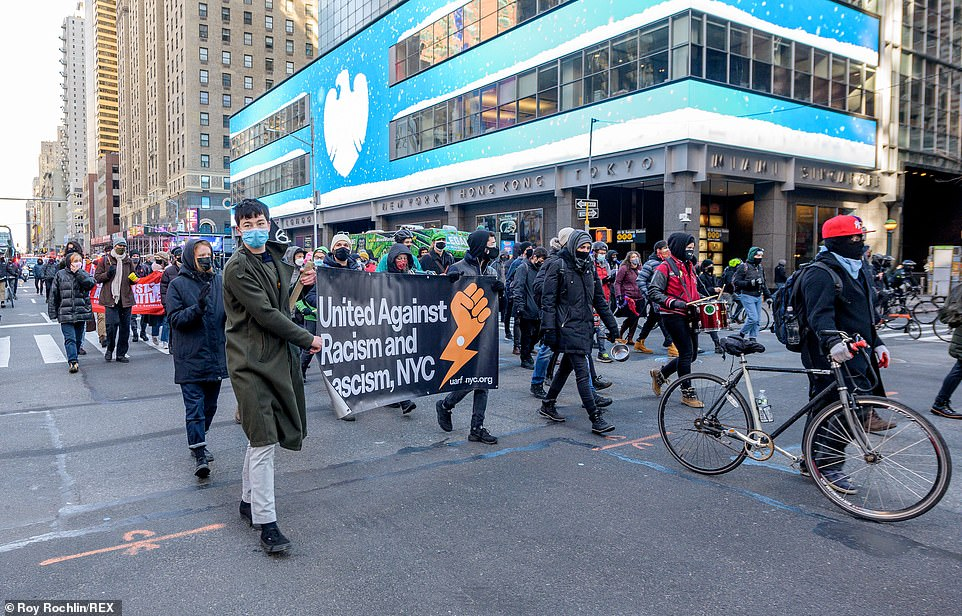Masked protesters carried a banner saying 'United Against Racism and Fascism, NYC' past a Barclays building in Manhattan